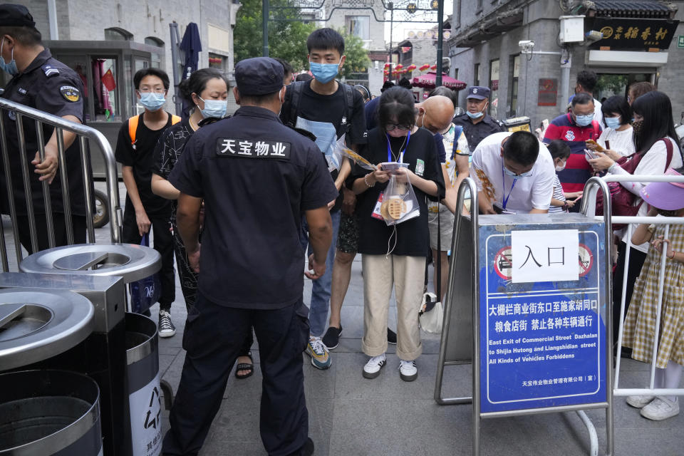 People scan health check codes with their smartphones to show to a security guard at a tourist shopping street in Beijing, Tuesday, Aug. 3, 2021. Chinese authorities announced Tuesday mass coronavirus testing in Wuhan as an unusually wide series of COVID-19 outbreaks reached the city where the disease was first detected in late 2019. The current outbreaks, while still in the hundreds of cases in total, have spread much more widely than previous ones, reaching multiple provinces and cities including the capital, Beijing. (AP Photo/Mark Schiefelbein)