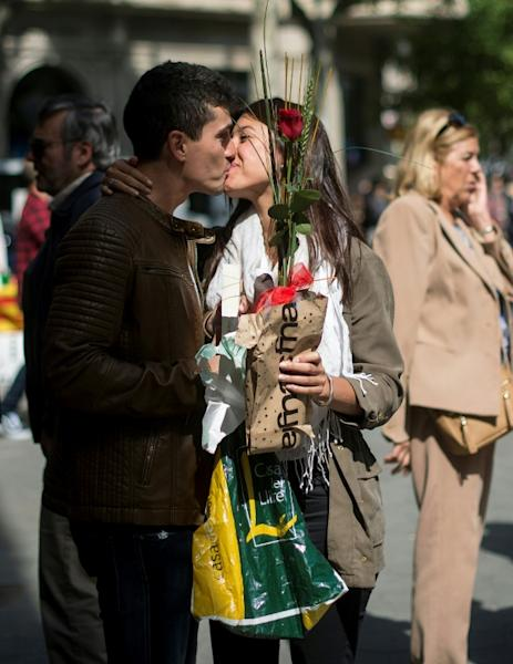 Couples stroll through the streets of Barcelona, exchanging gifts and kisses under sunny spring skies