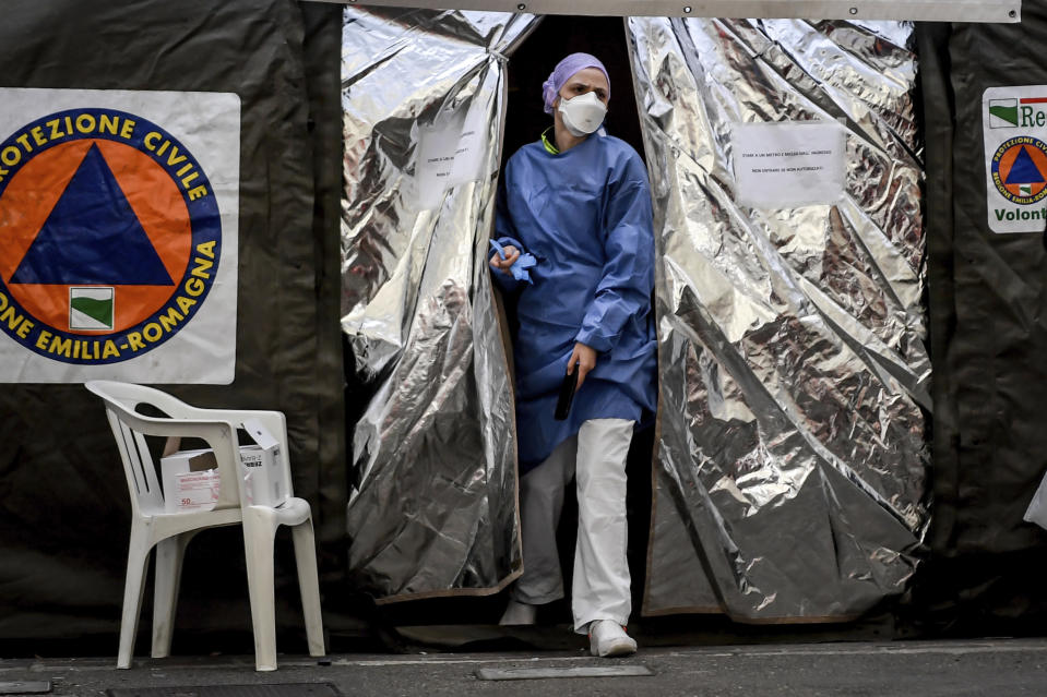 A paramedic wearing a mask gets out of a tent set up by the Italian Civil Protection outside the emergency ward of the Piacenza hospital, northern Italy, Thursday, Feb. 27, 2020. Italy is changing how it reports coronavirus cases and who will get tested in ways that could lower the country's caseload even as an outbreak centered in northern Italy spreads in Europe. (Claudio Furlan/Lapresse via AP)
