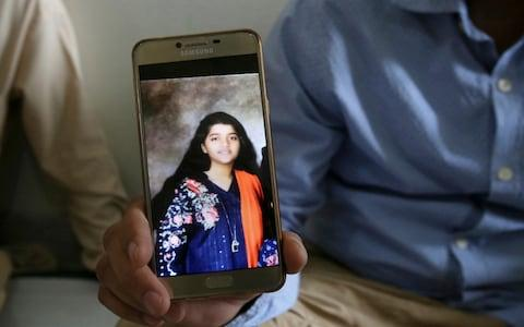 The father of Sabika Sheikh displays her picture on his phone at his home in Karachi, Pakistan - Credit: Fareed Khan/AP
