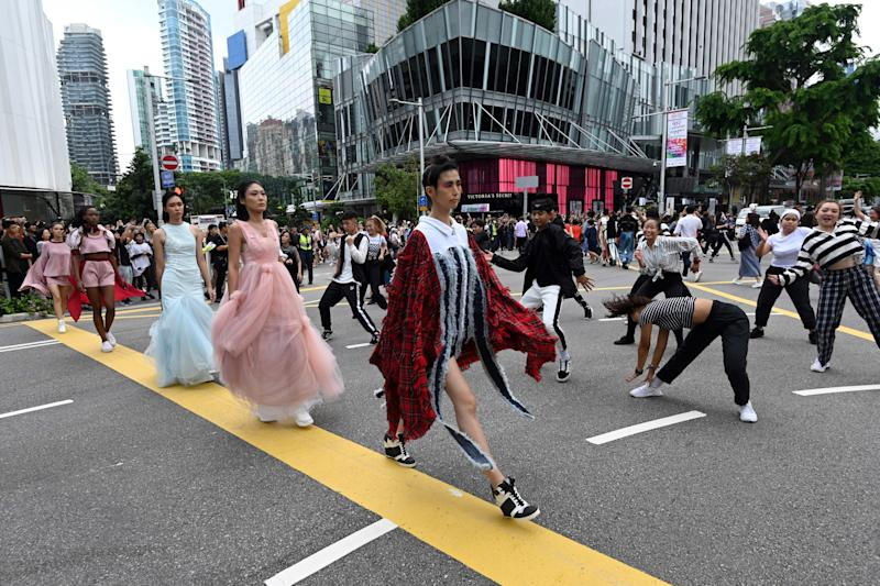 "Models display retail fashion as they walk across the traffic junction of Orchard Road during the launch of the ""Great Singapore Sale"" in Singapore on June 21, 2019. (Photo by Roslan RAHMAN / AFP) (Photo credit should read ROSLAN RAHMAN/AFP via Getty Images)"