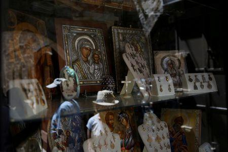 Tourists are reflected in the window of a shop selling Christian souvenirs in the Christian Quarter of Jerusalem's Old City June 21, 2016. REUTERS/Ronen Zvulun