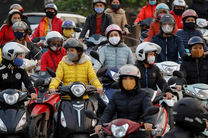 Labourers wearing protective masks gather while they wait for a ferry on the way home after work, despite a government rule on social distancing during the coronavirus disease (COVID-19) outbreak in Hai Duong province, Vietnam April 7, 2020. REUTERS/Kham TPX IMAGES OF THE DAY