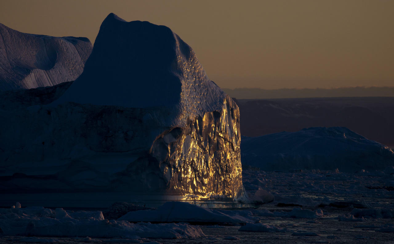 In this July 19, 2011 picture, the midnight sun illuminates an iceberg, among the many shed daily into the sea from the Jakobshavn Glacier in Ilulissat, Greenland. Greenland is the focus of many researchers trying to determine how much its melting ice may raise sea levels. (AP Photo/Brennan Linsley)