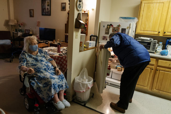 """Meals on Wheels driver Jim Stotler, right, puts away a meal he delivered to Phyllis Antonelli, 90, at her apartment in, in Pawtucket, R.I, Friday, Nov. 20, 2020. Stotler, who delivers dozens of meals daily for Meals on Wheels of Rhode Island, said he worries about the isolation that some of his clients suffered even before the pandemic. And now during the pandemic many of the people he sees haven't been able to see their families as much as they'd like or go to events like weddings. """"The hardest part for me is knowing I can't spend a lot of time with them,"""" he said. On one of his routine visits in 2016, Stotler found her laying on the floor where she'd been for 15 hours after falling and quickly called paramedics. (AP Photo/David Goldman)"""
