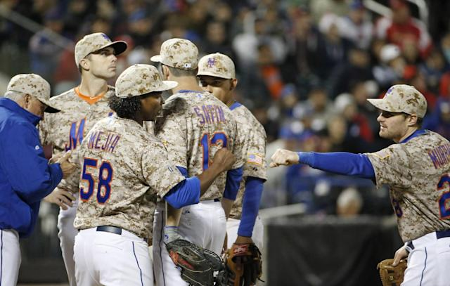 New York Mets second baseman Daniel Murphy (28) congratulates Mets starting pitcher Jenrry Mejia (58) after New York Mets manager Terry Collins, far left, took Mejia out in the seventh inning of a baseball game against the St. Louis Cardinals in New York, Monday, April 21, 2014. Mets third baseman David Wright, second from left, looks to see who will relieve Mejia. (AP Photo/Kathy Willens)