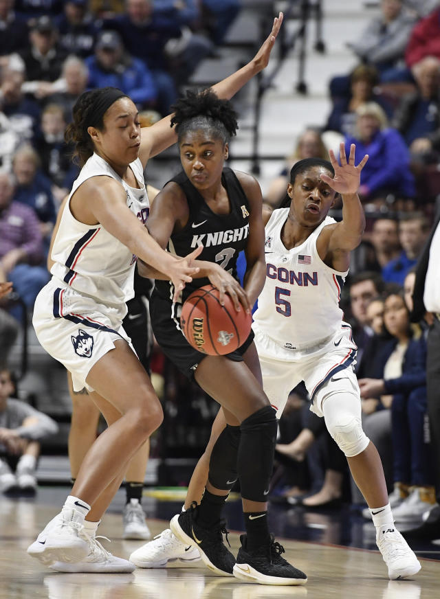 Central Florida's Kay Kay Wright, center, is pressured by Connecticut's Napheesa Collier, left, and Crystal Dangerfield, right, during the first half of an NCAA college basketball game in the American Athletic Conference women's tournament finals, Monday, March 11, 2019, at Mohegan Sun Arena in Uncasville, Conn. (AP Photo/Jessica Hill)