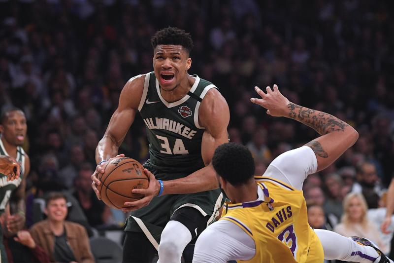 Milwaukee Bucks forward Giannis Antetokounmpo, knocks down Los Angeles Lakers forward Anthony Davis as he drives to the basket during the first half of an NBA basketball game Friday, March 6, 2020, in Los Angeles. (AP Photo/Mark J. Terrill)
