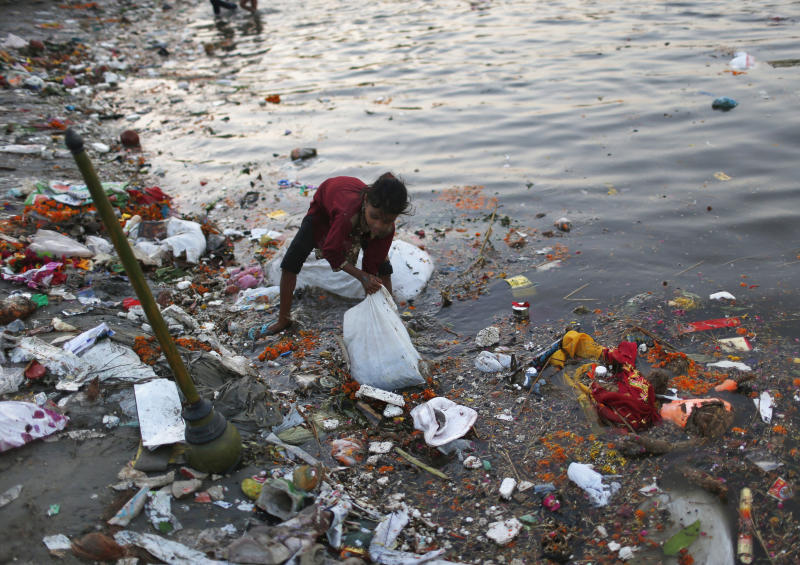 A girls collects items thrown in as offerings by devotees in the waters of the Yamuna river on the last day of the Ganesh Chaturthi festival in New Delhi. (Photo: Ahmad Masood/Reuters)