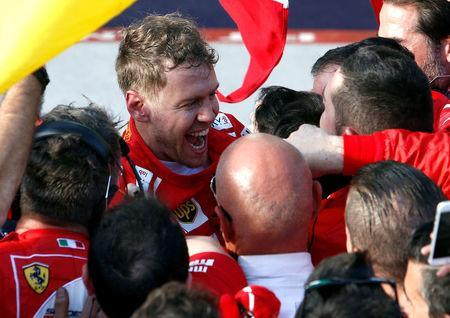 Formula One - F1 - Australian Grand Prix - Melbourne, Australia - 26/03/2017 - Ferrari driver Sebastian Vettel of Germany celebrates with members of his team after winning the Australian Grand Prix. REUTERS/Brandon Malone