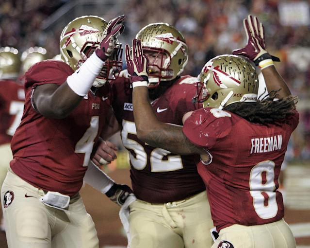 Florida State running back Devonta Freeman (8) celebrates with tight end Giorgio Newberry (4) and offensive linesman Bryan Stork (52) after scoring on a 5-yard touchdown run against Miami during the first quarter of an NCAA college football game Saturday, Nov. 2, 2013, in Tallahassee, Fla. (AP Photo/Steve Cannon)