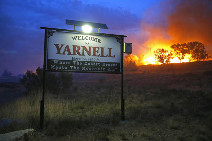 FILE - In this June 30, 2013 file photo, a wildfire burns homes in Yarnell, Ariz. The wildfire that began with a lightning strike and caused little immediate concern because of its remote location and small size quickly blazed into an inferno, leading officials to rapidly order more resources in the hours before flames killed 19 members of an elite Hotshot crew, according to a report released Monday, July 15, 2013. (AP Photo/The Arizona Republic, David Kadlubowski, File)