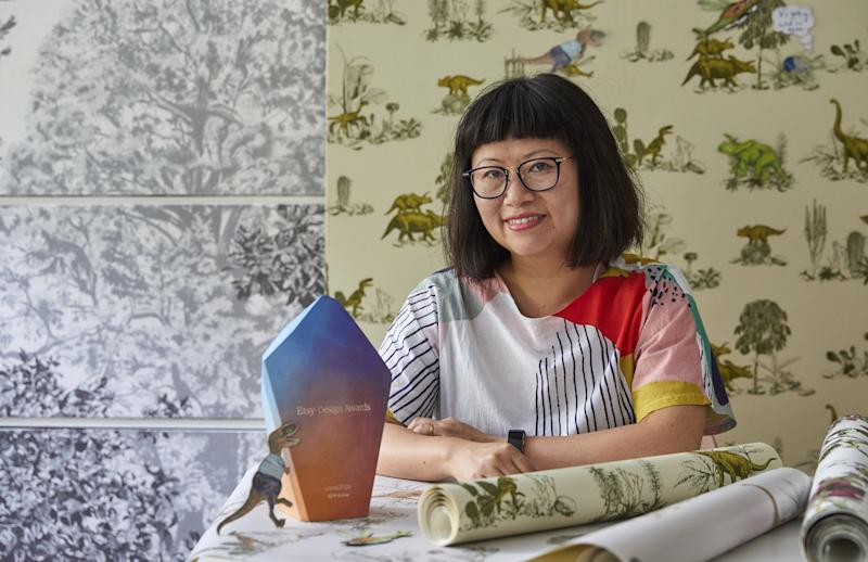 Sian Zeng sits in front of a wall decorated with dinosaur print green wallpaper with a pink and purple award on her desk
