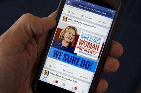 A mobile phone shows a Facebook page of campaign propaganda to promote Hillary Clinton as president in 2016, in this photo illustration taken April 13, 2015. REUTERS/Mike Segar