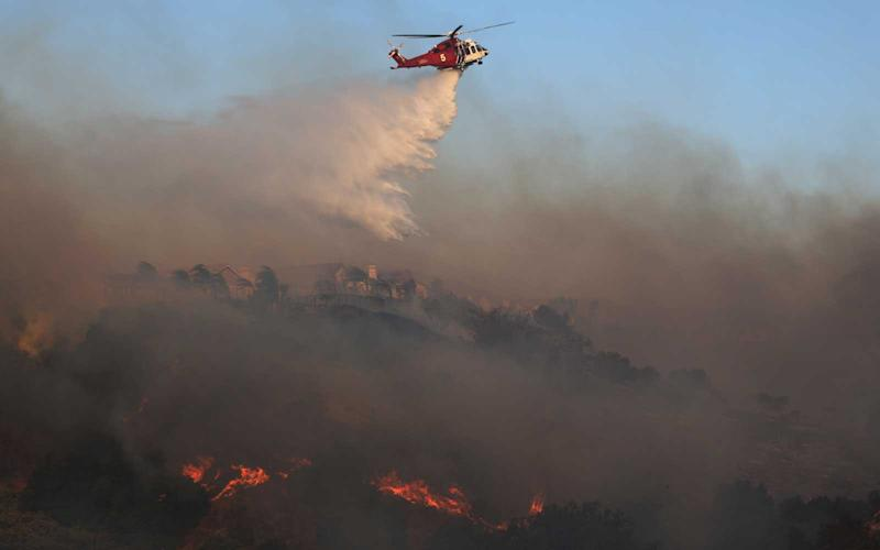 A firefighting helicopter works the Saddleridge Fire on October 11, 2019 near Porter Ranch, California. | Mario Tama/Getty Images
