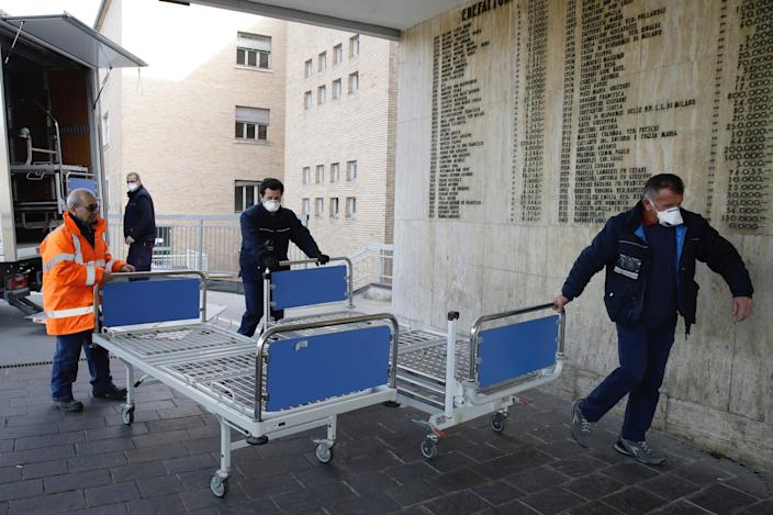 Personnel carry new beds inside the hospital of Codogno, near Lodi in Northern Italy, Friday, Feb. 21,2020.