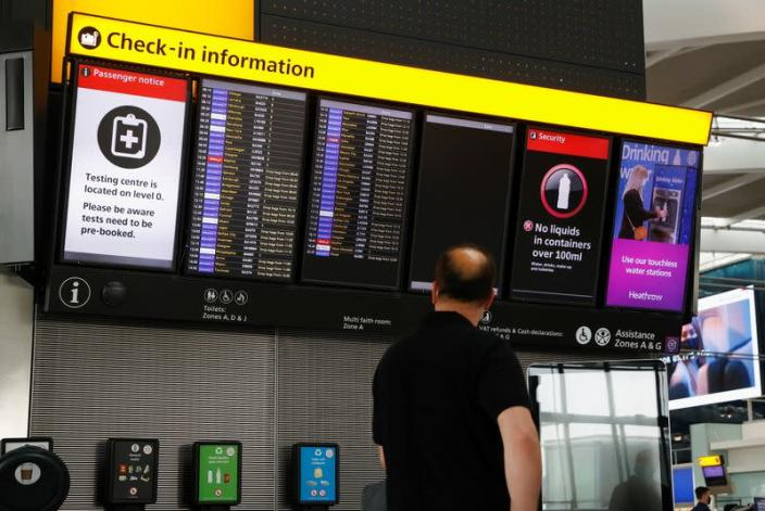FILE PHOTO: A man looks at a check-in information board at Heathrow Airport in London