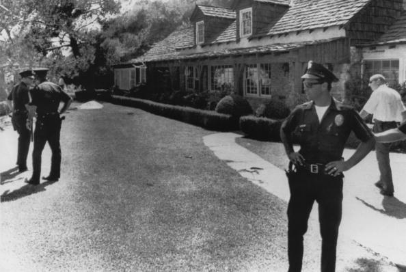 <p>Policemen stand guard outside the home of film director Roman Polanski in west Los Angeles, following the murder of his wife Sharon Tate, and four other people by Charles Manson and his 'family', August 1969.</p>