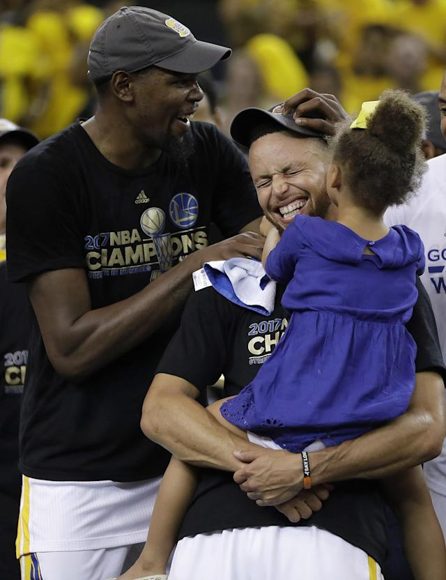 <p>Golden State Warriors guard Stephen Curry, center, holds his daughter Riley as they celebrate with forward Kevin Durant, left, after Game 5 of basketball's NBA Finals against the Cleveland Cavaliers in Oakland, Calif., Monday, June 12, 2017. The Warriors won 129-120 to win the NBA championship. (AP Photo/Marcio Jose Sanchez) </p>