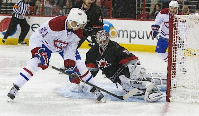 Montreal Canadiens' Lars Eller (81) flips the puck past Carolina Hurricanes goalie Cam Ward for a goal during the first period of an NHL hockey game in Raleigh, N.C., Tuesday, Dec. 31, 2013. (AP Photo/Karl B DeBlaker)