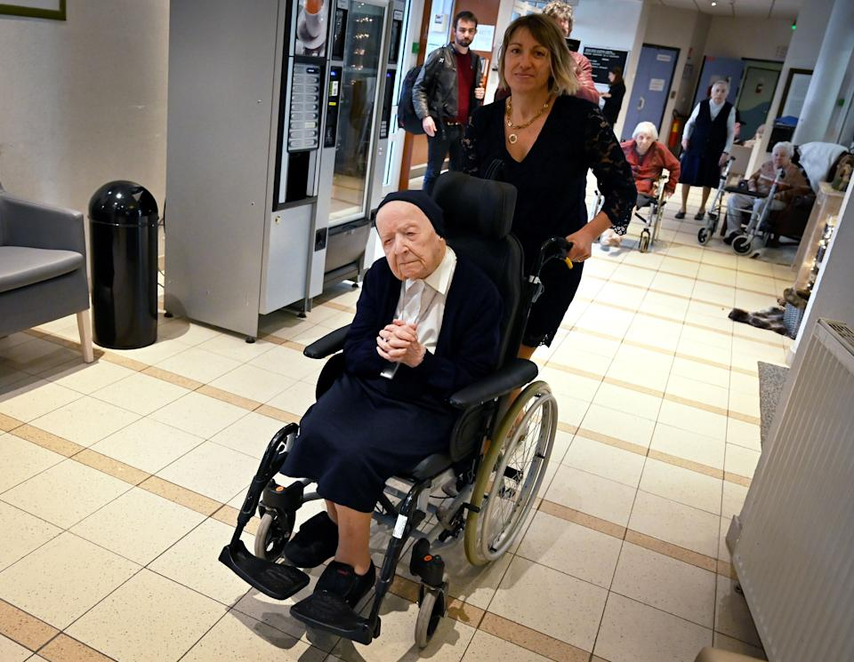 Sister Andre (C), Lucille Randon in the registry of birth, the eldest French citizen, is pushed in a wheelchair during an event to celebrate her 116th birthday in the EHPAD (Housing Establishment for Dependant Elderly People) in Toulon, southern France, where she has been living since 2009. - Sister Andre was born February 11, 1904. (Photo by GERARD JULIEN / AFP) (Photo by GERARD JULIEN/AFP via Getty Images)