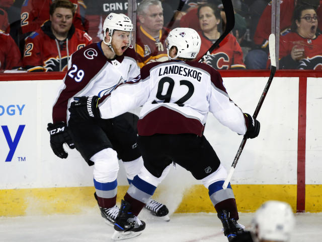 Colorado Avalanche center Nathan MacKinnon (29) celebrates his game-winning goal against the Calgary Flames with teammate Gabriel Landeskog (92) during overtime of an NHL hockey playoff game in Calgary, Alberta, Saturday, April 13, 2019. (Jeff McIntosh/The Canadian Press via AP)