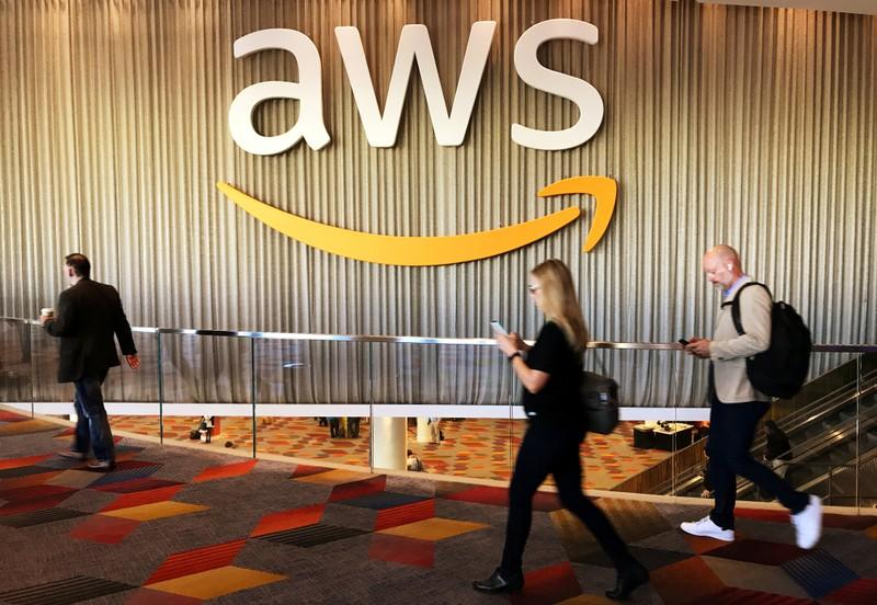 FILE PHOTO: Attendees at Amazon.com Inc annual cloud computing conference walk past the Amazon Web Services logo in Las Vegas