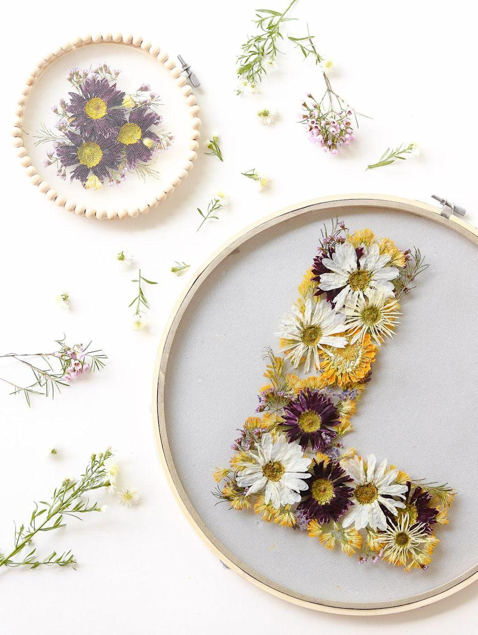 """<p>The beauty about pressed flowers is that you turn them into just about anything. In this case, seal flowers between two sheets of tulle inside a hoop and hang somewhere it'll be seen. </p><p><em><a href=""""https://www.lilyardor.com/pressed-floral-hoops/"""" rel=""""nofollow noopener"""" target=""""_blank"""" data-ylk=""""slk:Get the tutorial at Lily Ardor »"""" class=""""link rapid-noclick-resp"""">Get the tutorial at Lily Ardor » </a></em></p>"""