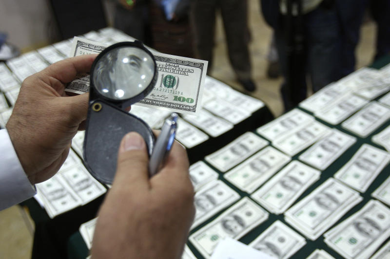 FILE - In this Aug. 17, 2012 file photo, a police officer inspects an alleged counterfeit $100 U.S. dollar note during a media presentation in Lima, Peru. With its meticulous criminal craftsmen, cheap labor and, by some accounts, less effective law enforcement, Peru has in the past two years overtaken Colombia as the No. 1 source of counterfeit U.S. dollars, says the U.S. Secret Service, protector of the world's most widely-traded currency. (AP Photo/Karel Navarro, File)