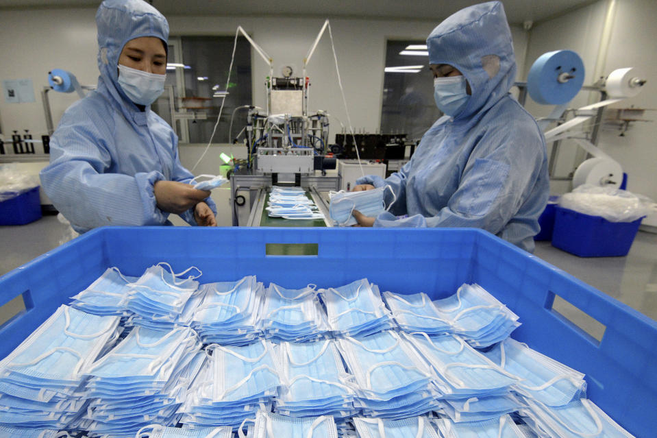 Workers wearing face masks to help curb the spread of the coronavirus arrange face masks from a machine at a factory in Handan city in north China's Hebei province on Jan. 8, 2021. China's economy grew 2.3% in 2020 as a recovery from the coronavirus pandemic accelerated while the United States, Europe and Japan struggled with disease flare-ups. (Chinatopix via AP)