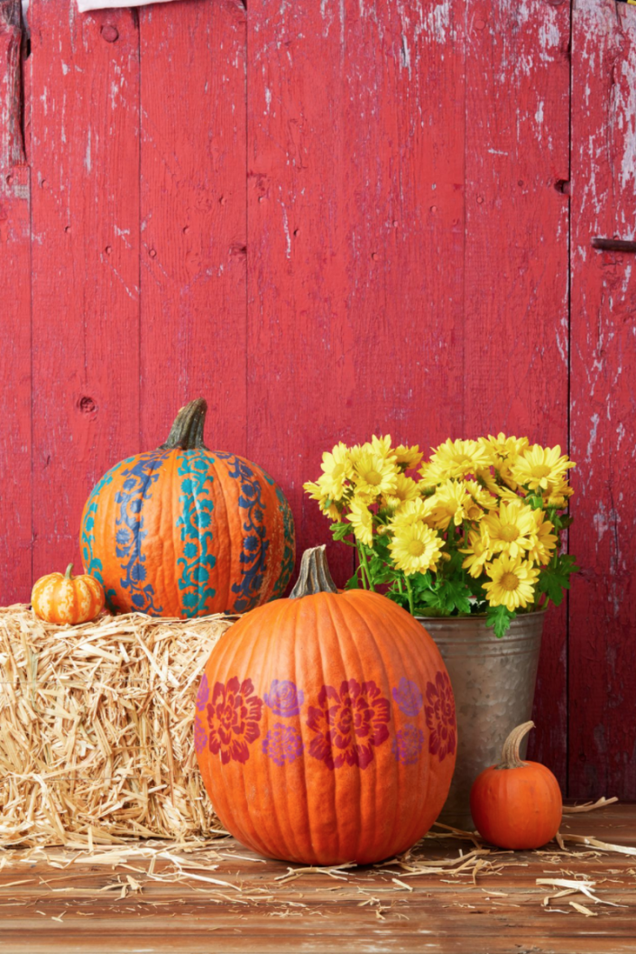 """<p>Who needs store-bought decorations when you've got these pumpkin masterpieces around? This craft is a striking way to decorate your entryway—and it's easy to tackle!</p><p><strong>Make the Pumpkins: </strong>Use painter's tape to outline several stripes (or one horizontal stripe) around an orange pumpkin. For vertical stripes, tape a flower stencil inside one of the stripes, then use a foam pouncer to lightly dab paint onto it. Let dry, then remove the stencil and tape it to the next section of the stripe. Continue until you fill in the entire stripe, then repeat for the other stripes, alternating colors. To make a horizontal stripe, cut out a large flower stencil and tape it inside the stripe. Using the pouncer, lightly dab paint onto the pumpkin to fill in the stencil. Let dry, then remove the stencil and use it several more times within the stripe. Repeat with two smaller stencils.</p><p><a class=""""link rapid-noclick-resp"""" href=""""https://go.redirectingat.com?id=74968X1596630&url=https%3A%2F%2Fwww.walmart.com%2Fsearch%2F%3Fquery%3Dcraft%2Bpaint&sref=https%3A%2F%2Fwww.thepioneerwoman.com%2Fhome-lifestyle%2Fdecorating-ideas%2Fg36732301%2Foutdoor-fall-decorations%2F"""" rel=""""nofollow noopener"""" target=""""_blank"""" data-ylk=""""slk:SHOP CRAFT PAINT"""">SHOP CRAFT PAINT</a></p>"""