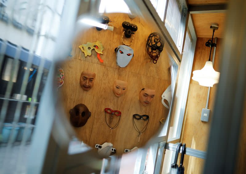 Masks based on real people's faces are reflected in a mirror at the Shuhei Okawara's mask shop Kamenya Omote in Tokyo