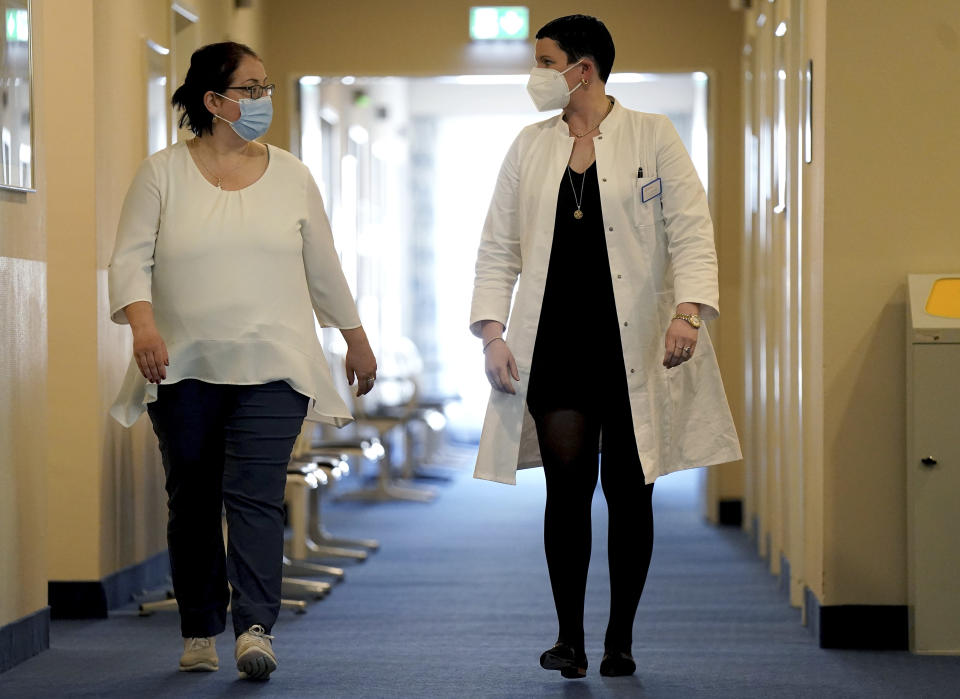 Joerdis Frommhold, right, head doctor of the 'MEDIAN Clinic Heiligendamm', speaks with patient Simone Ravera, left, after an interview with the Associated Press in Heiligendamm, northern Germany, Wednesday, April 14, 2021. The MEDIAN Clinic, specialized on lung diseases, treats COVID-19 long time patients from all over Germany. (AP Photo/Michael Sohn)