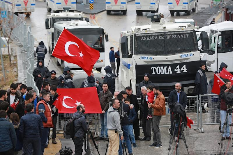 Demonstrators wave the Turkish national flag by a blockade of anti-riot police vehicles and a sealed off area surrounding the Dutch embassy in Ankara on March 12, 2017 (AFP Photo/Adem ALTAN)