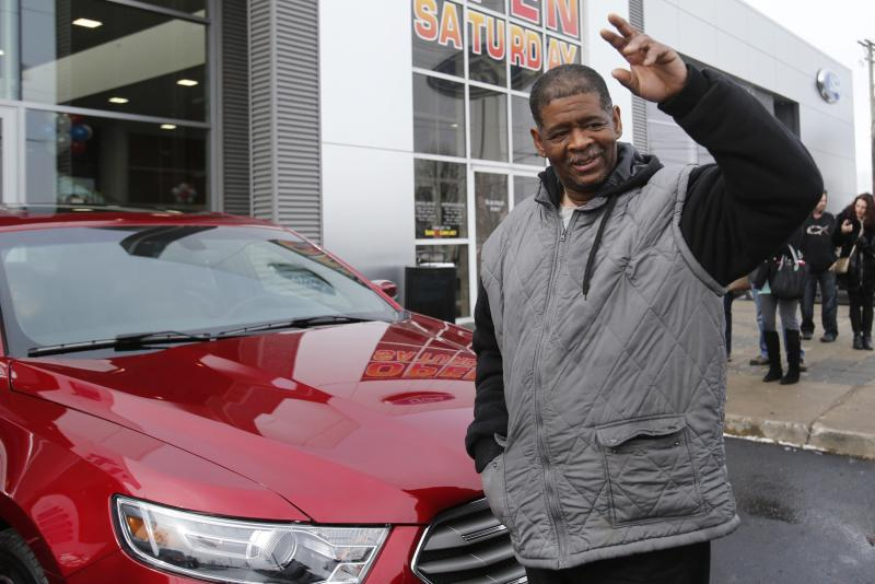 Detroit resident James Robertson waves to the crowd after being surprised with the free gift of a 2015 red Ford Taurus sedan, at the Suburban Ford dealership in Sterling Heights, Michigan, February 6, 2015. The 56-year-old factory worker, known for walking 21 miles to get to and from work for 9 years, is also the recipient of about $300,000 in donations raised by a college student after his story was widely publicized in local media. REUTERS/Rebecca Cook (UNITED STATES - Tags: TRANSPORT SOCIETY)