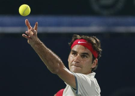 Roger Federer of Switzerland serves to Lukas Rosol of the Czech Republic during their men's singles match at the ATP Dubai Tennis Championships, February 27, 2014. REUTERS/Saleh Salem