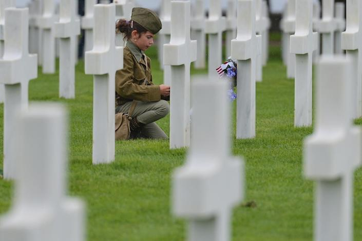 <p>A girl looks at the graves of fallen soldiers at the Normandy American Cemetery, which contains the remains of 9,387 American military dead, most killed during the invasion of Normandy and ensuing military operations in World War II.<br> (Photo: Artur Widak/NurPhoto via Getty Images) </p>