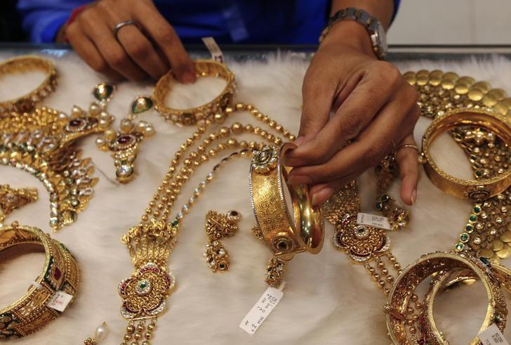 A woman looks at a gold bangle inside a jewellery showroom at a market in Mumbai