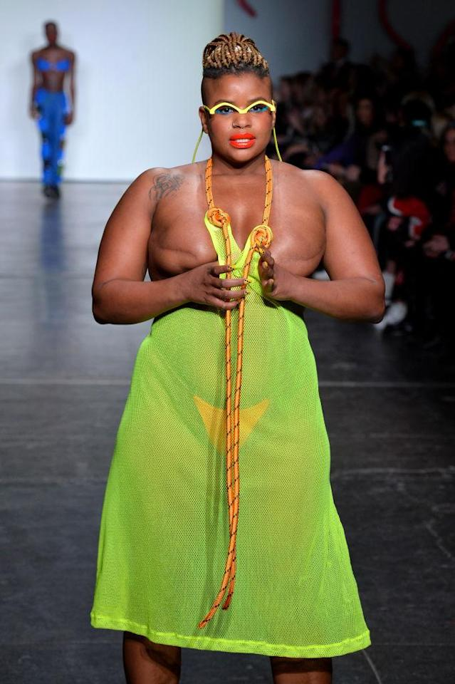 <p>Model with visible breast scars wears a green netted dress with orange rope details and orange bikini bottom for Chromat's Fall 2018 show. (Photo: Getty) </p>