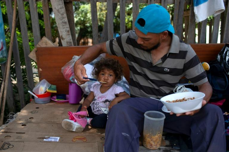 A Venezuelan and his daughter camping on the side of the road in Boa Vista, in the Brazilian state of Roraima