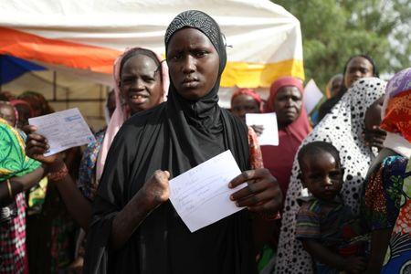 Woman is seen with a food ration card in a queue to receive food supplement from WFP at the Banki IDP camp, Borno