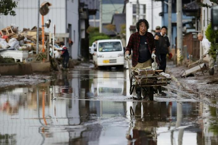 A man removes muddy items at a flood-affected area in Nagano -- Japan's government pledged financial support to affected regions without specifying how much aid it would set aside (AFP Photo/STR)