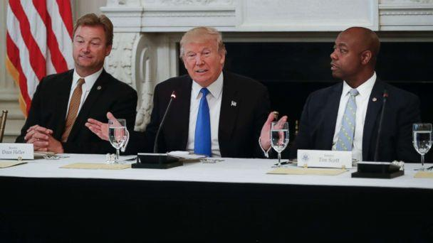 PHOTO: President Donald Trump, flanked by Sen. Dean Heller, R-Nev., left, and Sen. Tim Scott, R-S.C.,speaks at a luncheon with GOP leadership, July 19, 2017, in the State Dining Room of the White House in Washington. (Pablo Martinez Monsivais/AP)