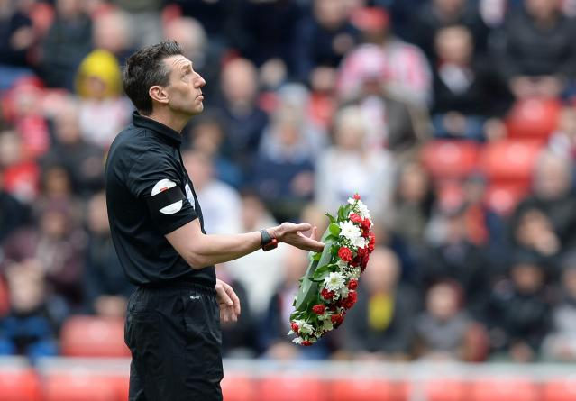 "Referee Lee Probert carries a wreath in memory of the Hillsborough disaster ahead of the English Premier League soccer match between Sunderland and Everton at the Stadium of Light in Sunderland, northern England April 12, 2014. REUTERS/Nigel Roddis (BRITAIN - Tags: SPORT SOCCER) FOR EDITORIAL USE ONLY. NOT FOR SALE FOR MARKETING OR ADVERTISING CAMPAIGNS. NO USE WITH UNAUTHORIZED AUDIO, VIDEO, DATA, FIXTURE LISTS, CLUB/LEAGUE LOGOS OR ""LIVE"" SERVICES. ONLINE IN-MATCH USE LIMITED TO 45 IMAGES, NO VIDEO EMULATION. NO USE IN BETTING, GAMES OR SINGLE CLUB/LEAGUE/PLAYER PUBLICATIONS"