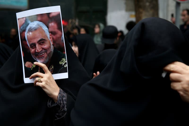 Iranian women react as they gather to mourn General Qassem Soleimani in Tehran