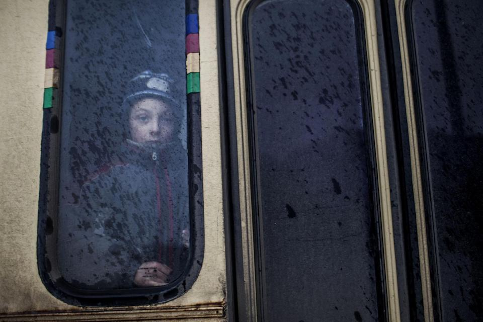 A young boy looks out of the window of a bus before fleeing the Ukrainian city of Debaltseve, in the Donetsk region, on February 1, 2015 (AFP Photo/Manu Brabo)
