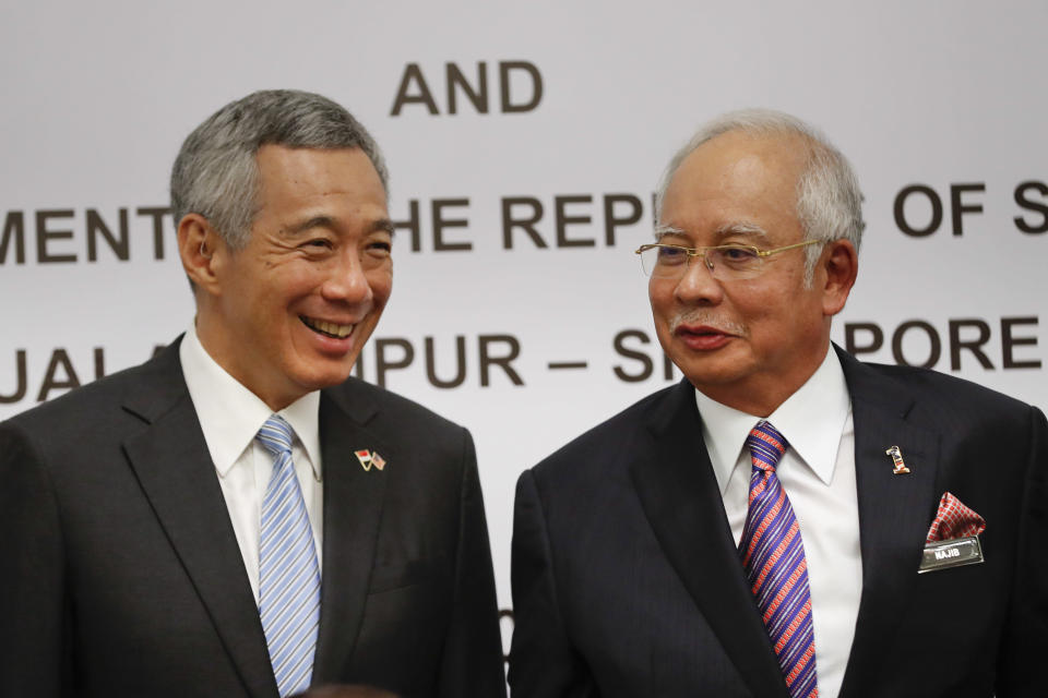 Singapore's Prime Minister Lee Hsien Loong, left, chats with Malaysia's Prime Minister Najib Razak during a signing ceremony of agreement on the Kuala Lumpur-Singapore High Speed Rail (HSR) project in Putrajaya, Malaysia, Tuesday, Dec. 13, 2016. Malaysia and Singapore today signed the long-awaited agreement on the Kuala Lumpur-Singapore High Speed Rail (HSR) project. (AP Photo/Vincent Thian)
