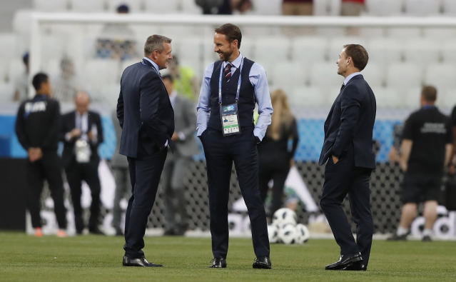 England head coach Gareth Southgate, center, smiles on the pitch prior the group G match between Tunisia and England at the 2018 soccer World Cup in the Volgograd Arena in Volgograd, Russia, Monday, June 18, 2018. (AP Photo/Frank Augstein)