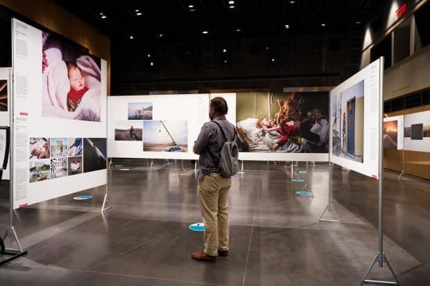 A journalist takes part in a media preview of the World Press Photo exhibit at the Canadian War Museum in Ottawa on Thursday. The exhibition showcases the year's best photojournalism and will be on display from July 23 to Aug. 15, 2021. (Sean Kilpatrick/The Canadian Press - image credit)