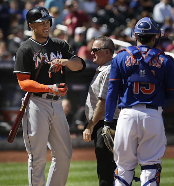 A trainer, center, examines Miami Marlins' Giancarlo Stanton's hand, left, after he was hit by a pitch while New York Mets catcher Travis d'Arnaud stands nearby during the fourth inning of the baseball game at Citi Field, Sunday, Sept. 15, 2013, in New York. (AP Photo/Seth Wenig)
